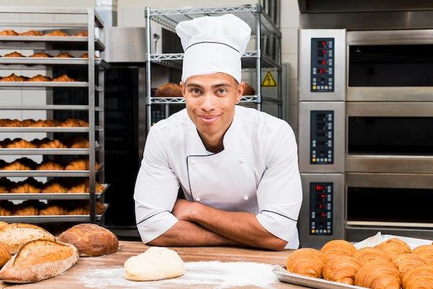 Portrait d'un jeune boulanger souriant, debout derrière la table avec un croissant frais et une miche de pain Photo gratuit