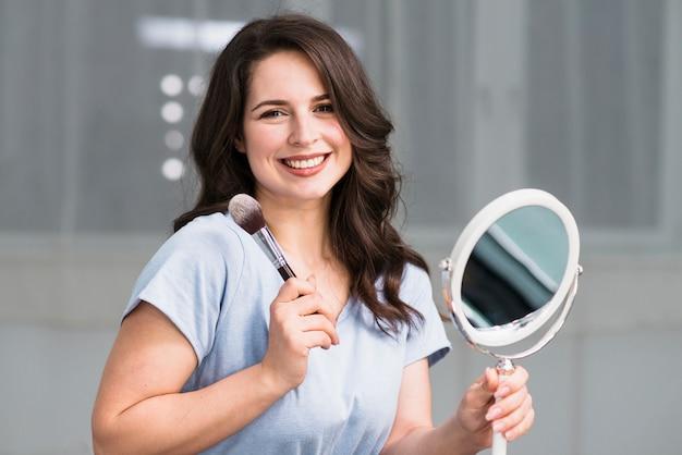 Portrait de jeune brune avec pinceau de maquillage et miroir Photo gratuit