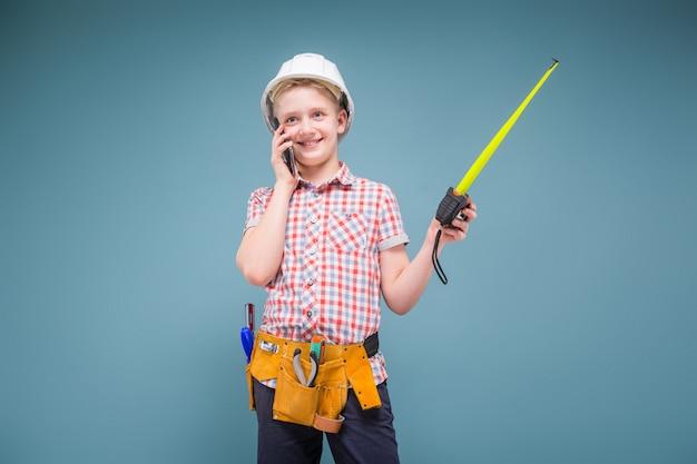 Portrait d'un jeune constructeur dans un casque et un ruban à mesurer à la main Photo Premium