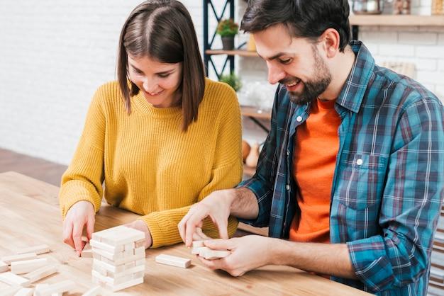 Portrait de jeune couple arrangeant les blocs de bois sur la table Photo gratuit