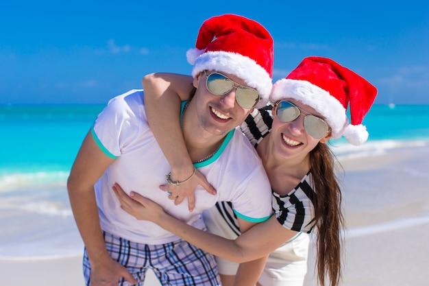 Portrait de jeune couple en chapeaux santa profiter de vacances à la plage Photo Premium