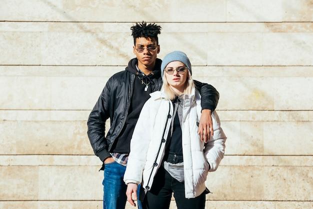 Portrait de jeune couple dans des vêtements à la mode, debout contre le mur Photo gratuit