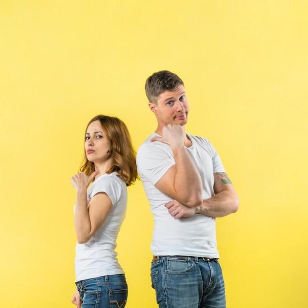 Portrait, de, jeune couple, debout, dos dos, projection, pouce haut, signe, à, autre Photo gratuit