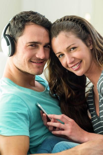 Portrait, de, jeune couple, écoute, musique, sur, téléphone portable, dans, salle de séjour Photo Premium
