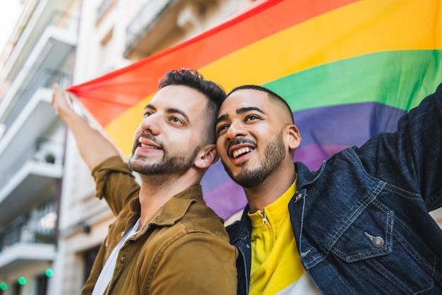 Portrait De Jeune Couple Gay Embrassant Et Montrant Leur Amour Avec Le Drapeau Arc-en-ciel Dans La Rue. Concept Lgbt Et Amour. Photo Premium