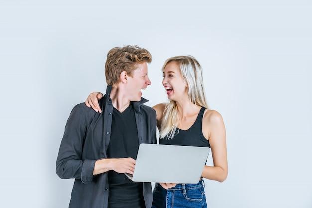 Portrait de jeune couple heureux à l'aide d'un ordinateur portable Photo gratuit