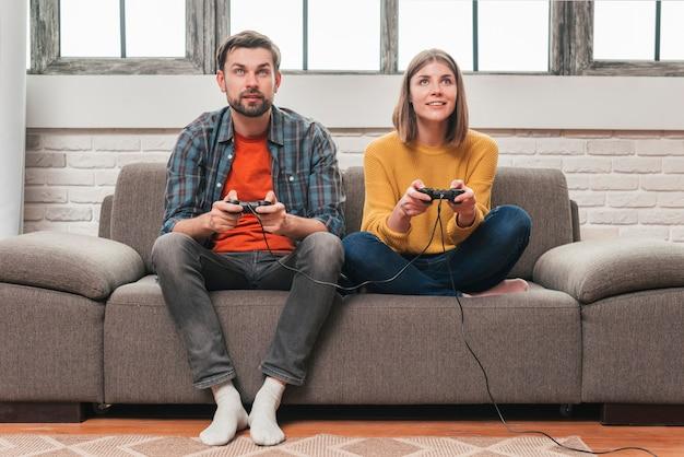 Portrait d'un jeune couple jouant au jeu vidéo avec des manettes de jeu Photo gratuit