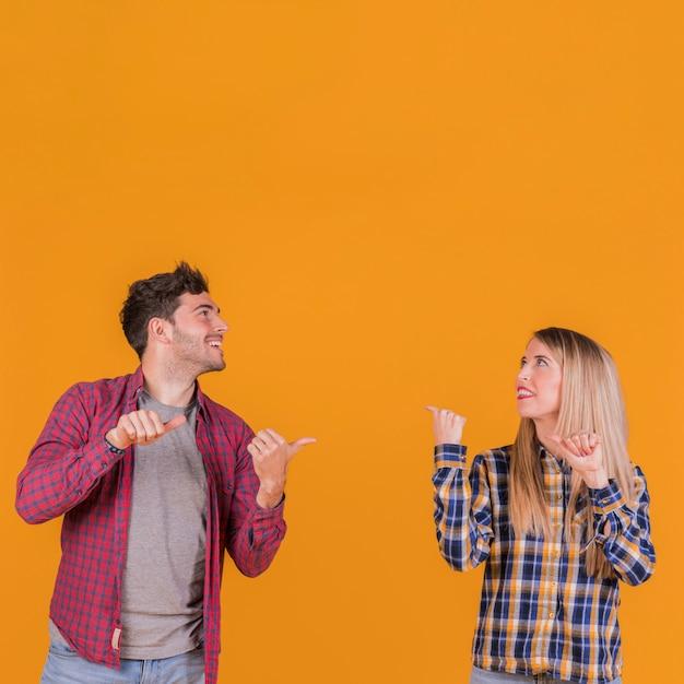Portrait, jeune, couple, projection, pouce, dos, dos, fond orange Photo gratuit
