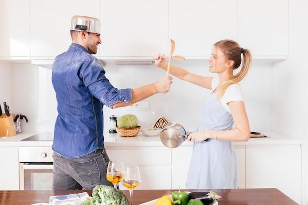 Portrait, de, a, jeune couple souriant, combats, à, ustensile, s'amuser, dans, les, cuisine Photo gratuit