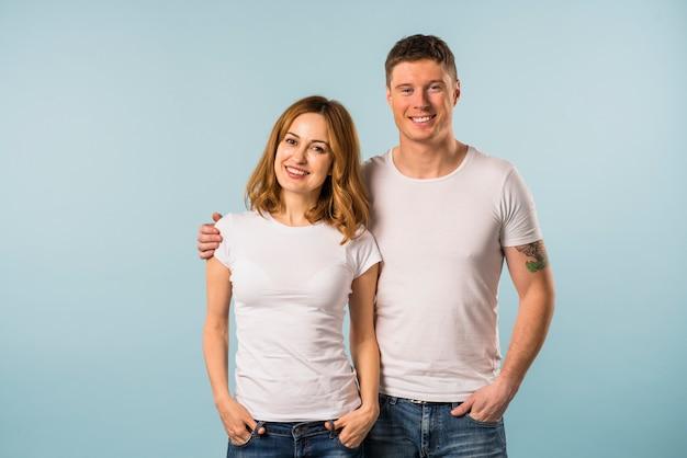 Portrait d'un jeune couple souriant sur fond bleu Photo gratuit