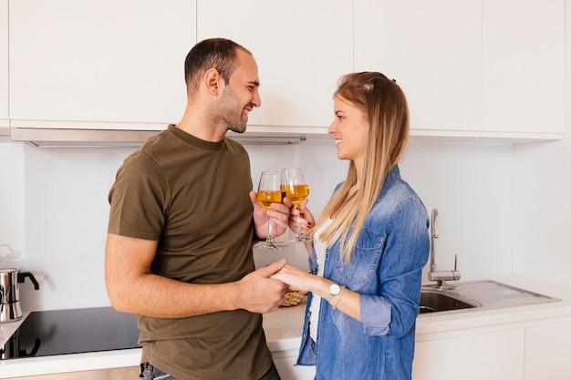 Portrait, de, a, jeune couple souriant, tenant main, autre, grillage, lunettes vin, dans cuisine Photo gratuit
