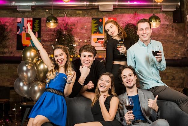 Portrait d'un jeune couple souriant tenant des verres à vin en profitant d'une fête Photo gratuit
