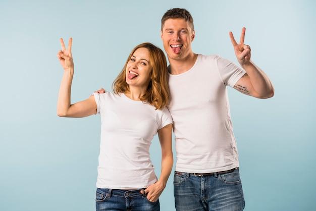 Portrait, jeune, couple, tirer langue, signe paix signe Photo gratuit