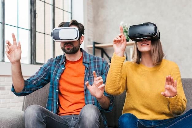 Portrait de jeune couple touchant dans l'air portant les lunettes de réalité virtuelle Photo gratuit