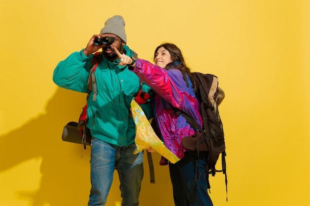 Portrait D'un Jeune Couple De Touristes Joyeux Isolé Sur Jaune Photo gratuit