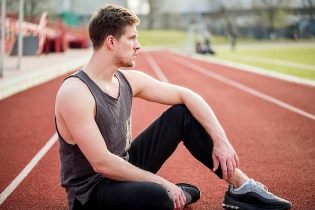 Portrait de jeune coureur assis sur la piste de course Photo gratuit