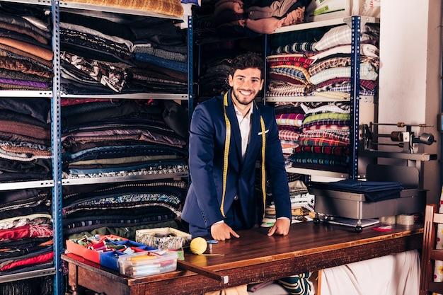 Portrait d'un jeune couturier souriant, regardant la caméra dans sa boutique Photo gratuit