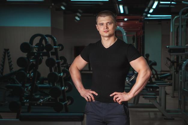 Portrait d'un jeune entraîneur de fitness musculaire beau se bouchent. Photo Premium