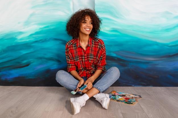 Portrait De Jeune étudiant Africain Assis Avec De Superbes Illustrations Dessinées à La Main En Acrylique Abstrait Au Studio. Photo gratuit