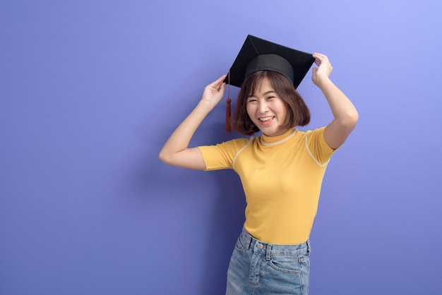 Un Portrait De Jeune étudiant Asiatique Portant Une Casquette De Graduation Sur Fond De Studio. Photo Premium