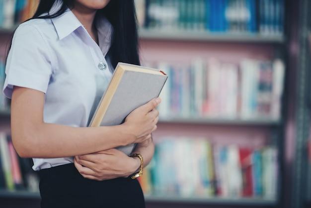 Portrait de jeune étudiant lisant un livre dans une bibliothèque Photo gratuit
