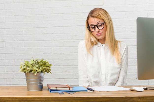 Portrait de jeune étudiante assise sur son bureau faisant des tâches en doutant et haussant les épaules Photo Premium