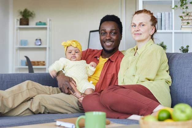 Portrait De Jeune Famille Heureuse Avec Nouveau-né Souriant à La Caméra Alors Qu'il était Assis Sur Un Canapé à La Maison Photo Premium