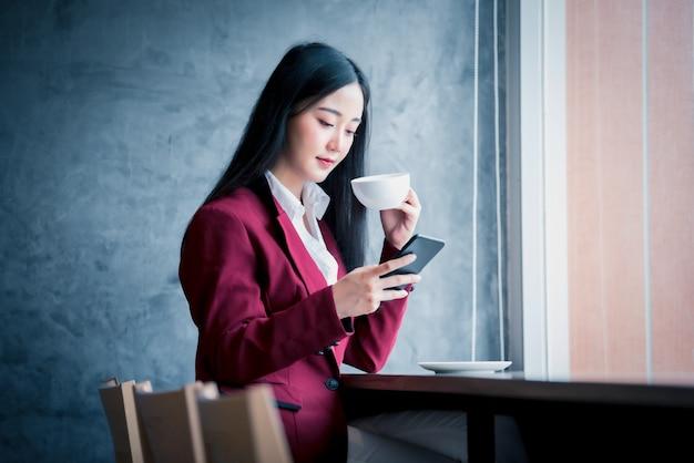 Portrait De Jeune Femme D'affaires Asiatique Assis à L'intérieur Dans Un Café, Boire Du Café à L'aide D'un Téléphone Intelligent. Concept De Réussite Commerciale. Photo Premium