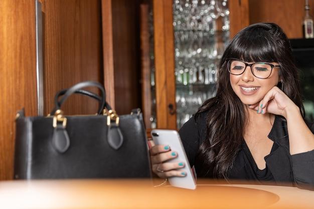 Portrait d'une jeune femme d'affaires attrayante textos un message sur son smatphone dans le café-bar. Photo Premium