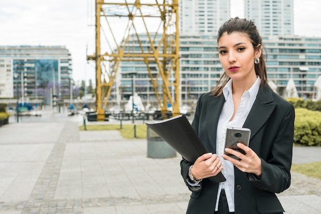 Portrait d'une jeune femme d'affaires détenant un téléphone intelligent et dossier à la main Photo gratuit