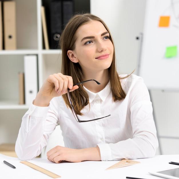 Portrait de jeune femme d'affaires avec des lunettes dans la pensée à la main Photo gratuit