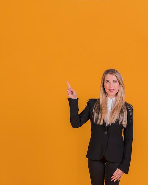 Portrait, jeune, femme affaires, pointage, doigt, contre, orange, toile de fond Photo gratuit