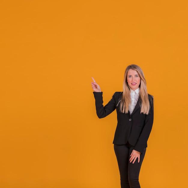 Portrait d'une jeune femme d'affaires pointant son doigt sur un fond orange Photo gratuit