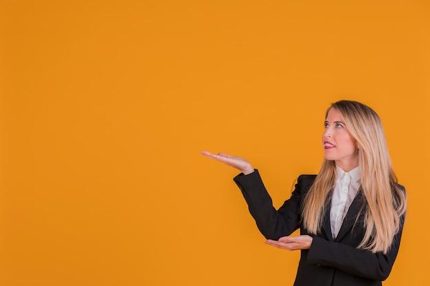 Portrait, jeune, femme affaires, présenter, quelque chose, contre, orange, toile de fond Photo gratuit