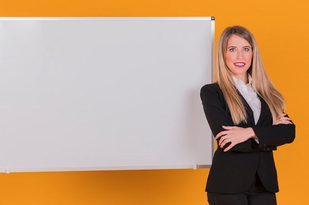 Portrait d'une jeune femme d'affaires réussie debout près du tableau blanc sur un fond orange Photo gratuit