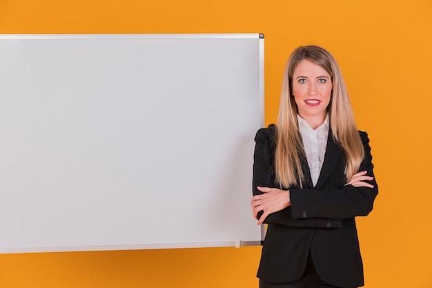 Portrait d'une jeune femme d'affaires réussie, debout près de tableau blanc sur un fond orange Photo gratuit