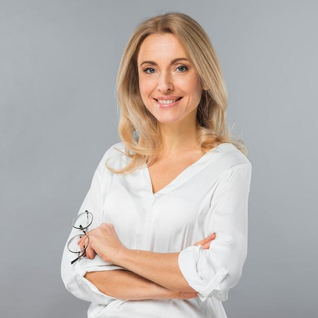 Portrait D'une Jeune Femme D'affaires Tenant Des Lunettes à La Main Sur Fond Gris Photo gratuit