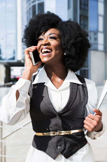 Portrait d'une jeune femme africaine parlant sur téléphone mobile Photo gratuit