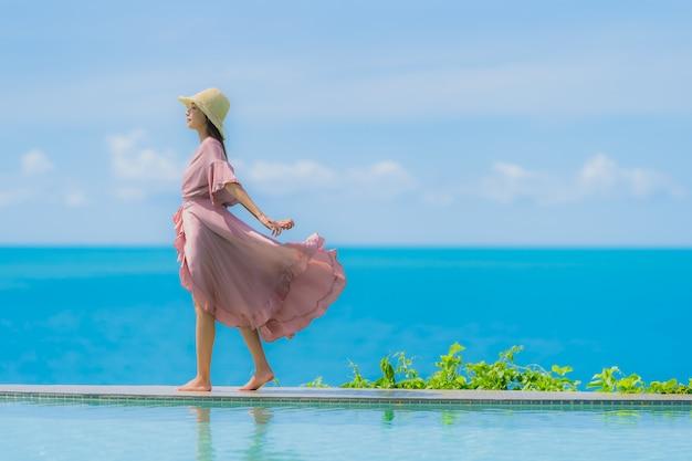 Portrait, jeune, femme asiatique, détendre, sourire, heureux, autour de, piscine extérieure, dans, hôtel, à, mer, vue océan Photo gratuit