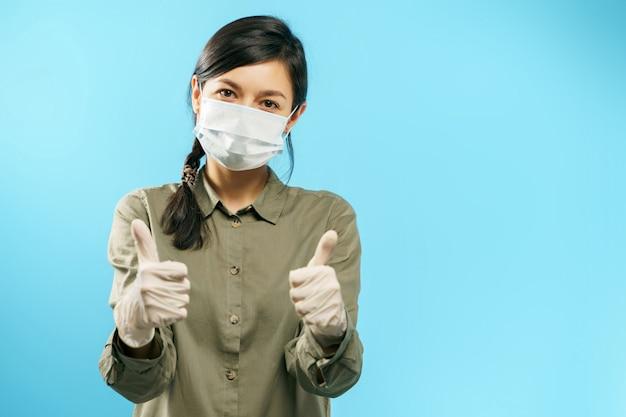 Portrait D'une Jeune Femme Asiatique En Masque De Protection Médicale Et Des Gants Montrant Le Pouce Vers Le Haut Sur Bleu Photo Premium