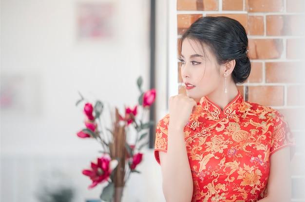 Portrait de jeune femme asiatique en robe rouge cheongsam traditionnel Photo Premium