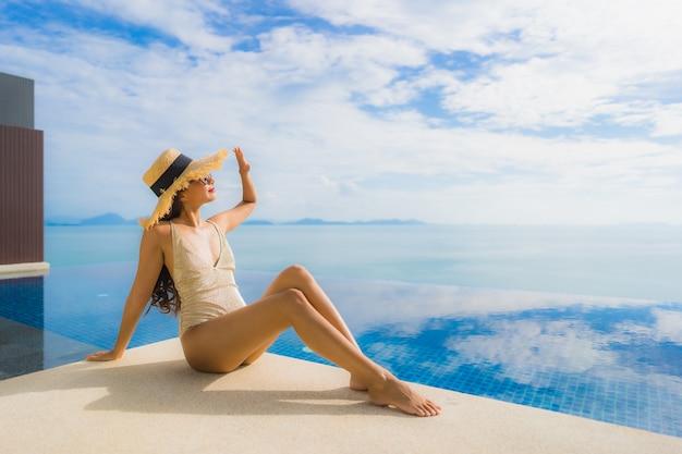 Portrait de jeune femme asiatique se détendre sourire heureux autour de la piscine dans l'hôtel et resort Photo gratuit