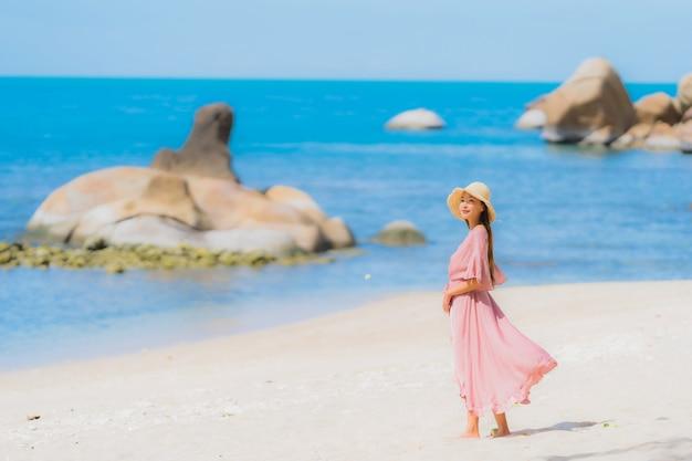 Portrait, jeune, femme asiatique, sourire, heureux, autour, plage, mer, océan, à, noix coco, palmier, pour, vacances Photo gratuit