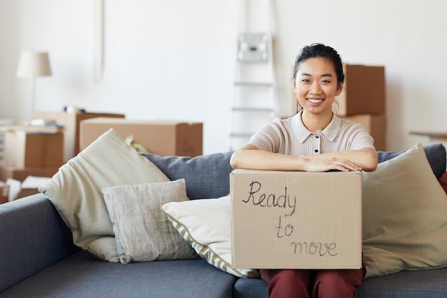 Portrait De Jeune Femme Asiatique Tenant Une Boîte En Carton Avec Inscription Prête à Déplacer Et Souriant à La Recherche Photo Premium