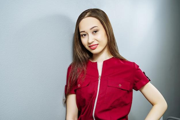 Portrait de jeune femme asiatique en uniforme sur fond gris Photo Premium