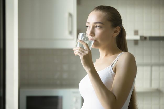 Portrait D'une Jeune Femme Attrayante Et Buvant De L'eau Photo gratuit