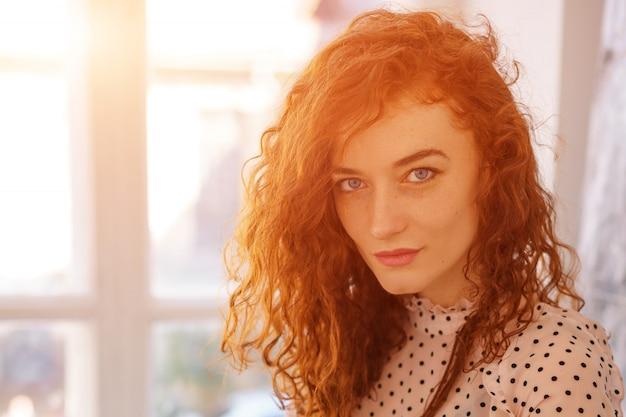 Portrait D'une Jeune Femme Aux Cheveux Rouges Sur La Fenêtre Photo Premium