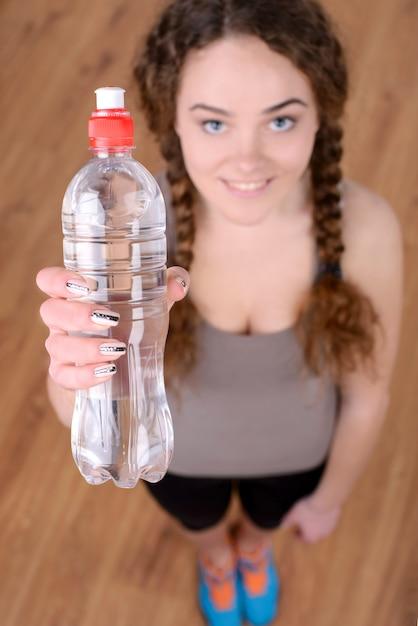 Portrait de jeune femme belle avec une bouteille d'eau. Photo Premium