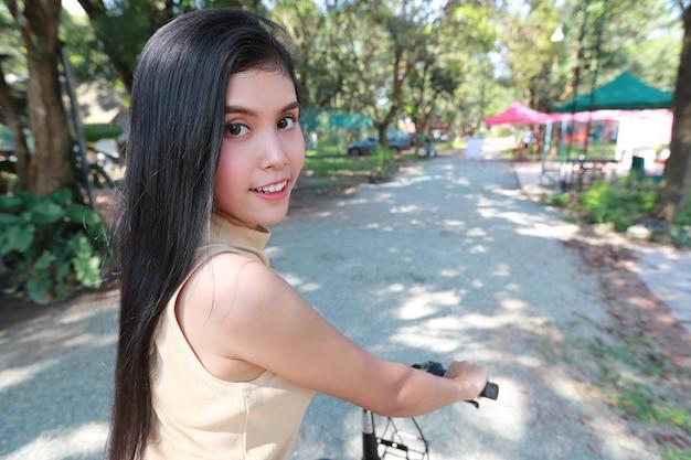 Portrait de jeune femme belle et hipster, vélo et s'amuser parmi la nature Photo Premium