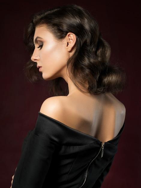 Portrait De Jeune Femme Belle Vêtue D'une Robe De Soirée Noire Posant Sur Fond Rouge Foncé Photo Premium
